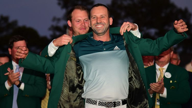 Sergio Garcia reçoit la veste verte, synonyme de victoire au Masters, des mains du vainqueur précédent : l'Anglais Danny Willett.  (HARRY HOW / GETTY IMAGES NORTH AMERICA)