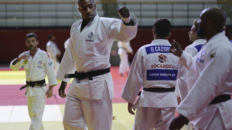 Teddy Riner salue ses coéquipiers avant de participer à un entraînement avec d'autres judokas français qualifiés pour les Jeux olympiques de Tokyo, à Paris, le 22 juin 2021. (THOMAS COEX / AFP)