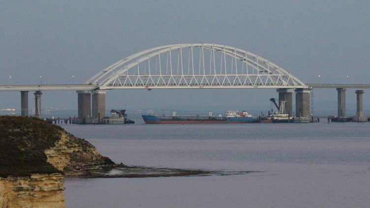 Un bateau de marchandises bloque le passage sous le pont de Crimée, devant le détroit de Kertch, qui sépare la Crimée de la Russie, le 25 novembre 2018. (ANDREJ KRYLOV / SPUTNIK / AFP)