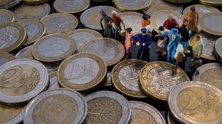 Image d'illustration montrant des figurines et des pièces de monnaie. (PHILIPPE HUGUEN / AFP)