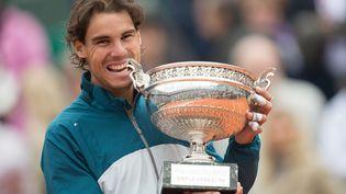 L'Espagnol Rafael Nadal croque dans le trophée après sa victoire à Roland-Garros, le 9 juin 2013. (JPDN / SIPA)
