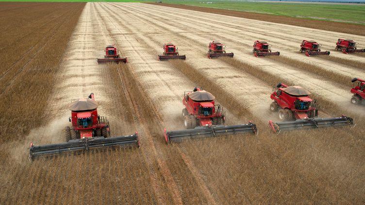 """Des tracteurs moissonnent un champ de soja à Campo Novo do Parecis, au Brésil, le 27 mars 2012. Le soja fait partie des16 matières premières""""dont les modes d'exploitation menacent directement 35 écorégions prioritaires"""",selon WWF. (YASUYOSHI CHIBA / AFP)"""