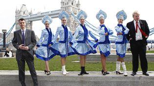 L'oligarque russe Mikhaïl Prokhorov et les danseuses du groupeZnaniye-Kalinka devant la Tour de Londres, le 4 mars 2011. (ANDREW WINNING / REUTERS)