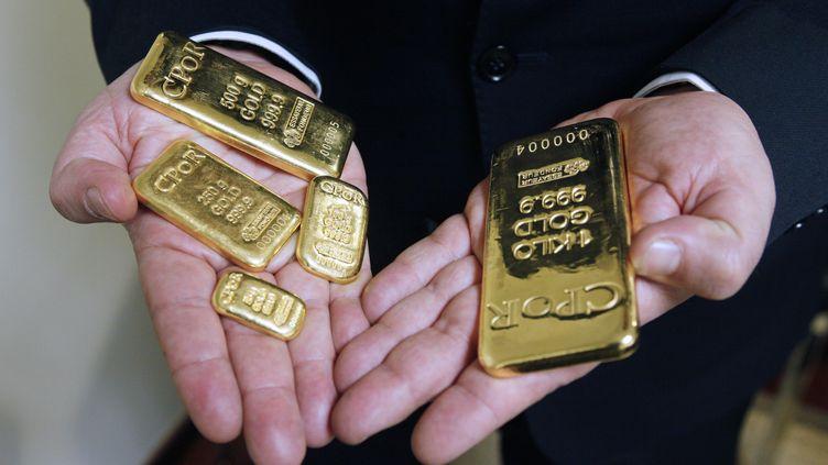 Differents lingots d'or dans les mains d'un homme. (THOMAS SAMSON / AFP)