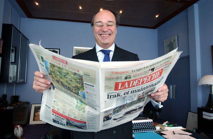 """Jean-Michel Baylet pose avec un exemplaire de """"La Dépêche du Midi"""", le 30 octobre 2003, à Toulouse (Haute-Garonne). (MAXPPP)"""