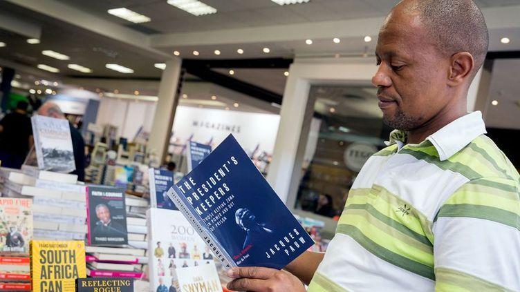 Un Sud-Africain découvre le livre du journaliste Jacques Pauw dans une librairie de Durban le jour de sa parution, le 29 octobre 2017. (Photo AFP/Rajesh Jantilal)