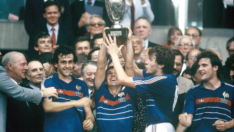 Victorieux de l'Espagne en finale de l'Euro 84, les Français Michel Platitni, Alain Giresse, Luis Fernandez et Bruno Bellone brandissent le trophée au Parc des Princes à Paris, le 27 juin 1984. (LEHR / SIPA)