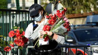 Une policière recueille les fleurs déposées pour Stéphanie M., en margede l'hommagele 26 avril 2021 à Rambouillet (Yvelines). (BERTRAND GUAY / AFP)