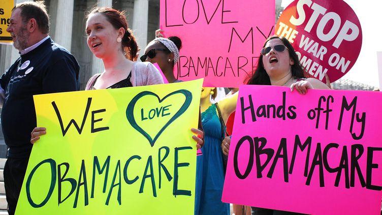 Des supporters de la réforme de l'assurance-santé de Barack Obama manifestent devant la Cour suprême des Etats-Unis, jeudi 28 juin, à Washington. (ALEX WONG / GETTY IMAGES NORTH AMERICA / AFP)