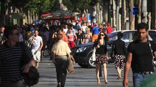 Des piétons arpentent les Champs-Elysées, à Paris (photographie non datée). (BRUCE YUANYUE BI / LONELY PLANET IMAGES / GETTY IMAGES)