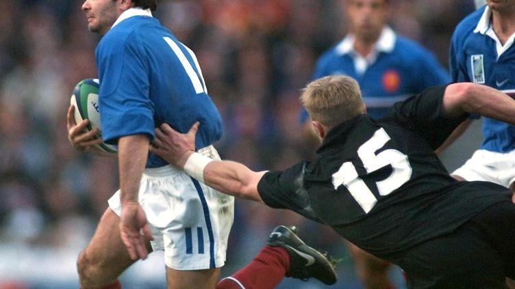 Christophe Dominici dans sa chevauchée fantastique lors de la Coupe du monde 1999 face aux All Blacks de Jeff Wilson (OLIVIER MORIN / FILES)