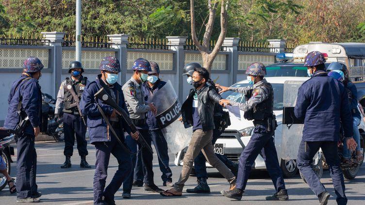Des policiers arrêtent un manifestant opposé au coup d'Etat militaire, le 9 février 2021 à Mandalay (Birmanie). (AFP)