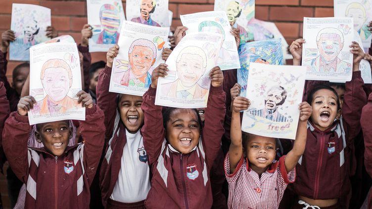 Des élèves brandissentdesdessins de l'ancien président Nelson Mandela à l'occasion de son anniversaire à Durban, le 18 juillet 2019. (RAJESH JANTILAL / AFP)