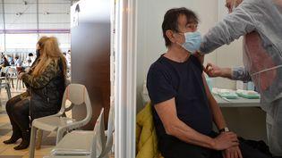 Un bénévole de l'Union nationale des réservistes formateurs du service de santé des armées injecte une dosedu vaccin Pfizer-BioNTech dans le bras d'un patient, le 7 avril 2021, au vaccinodrome de Toulouse. (YANN THOMPSON / FRANCEINFO)