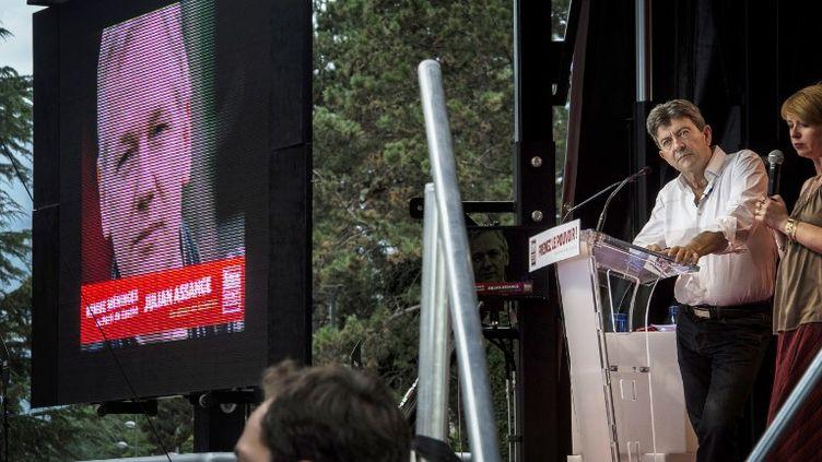 Julian Assange intervient par téléphone lors d'un meeting de Jean-Luc Mélenchon, le 24 août 2012. (JEFF PACHOUD / AFP)