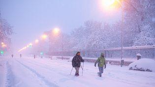 Des personnes marchent dans une rue de Madrid, recouverte par la neige après le passage de la tempête Filomena, samedi 9 janvier 2021. (Benjamin Cremel / AFP)