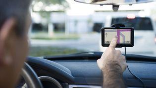 Un conducteur utilise un GPS au volant de sa voiture, le 17 juin 2017. (ODILON DIMIER / ALTOPRESS / AFP)