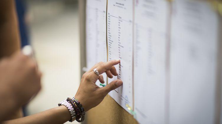 Une lycéenne cherche son nom sur la liste des résultats au baccalauréat, le 7 juillet 2015, à Paris. (MARTIN BUREAU / AFP)