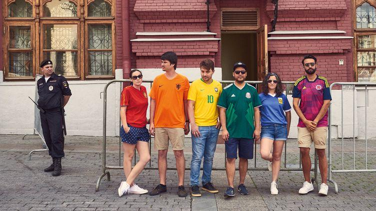 """Les six militants qui participent au projet """"The Hidden Flag"""" posent devant un policier, à Moscou (Russie), le week-end du 30 juin 2018. (JAVIER TLES / THE HIDDEN FLAG)"""