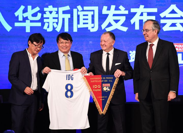 Jean-Michel Aulas, président de l'Olympique Lyonnais (2e D) et Xiong Xiaoge, associé fondateur d'IDG Capital Partners (2e G), lors d'une cérémonie à Pékin le 13 décembre 2016. La cérémonie a officialisé la prise de participation de 20 % du fonds d'investissement chinois IDG Capital Partners dans l'Olympique Lyonnais.   (GREG BAKER / AFP)