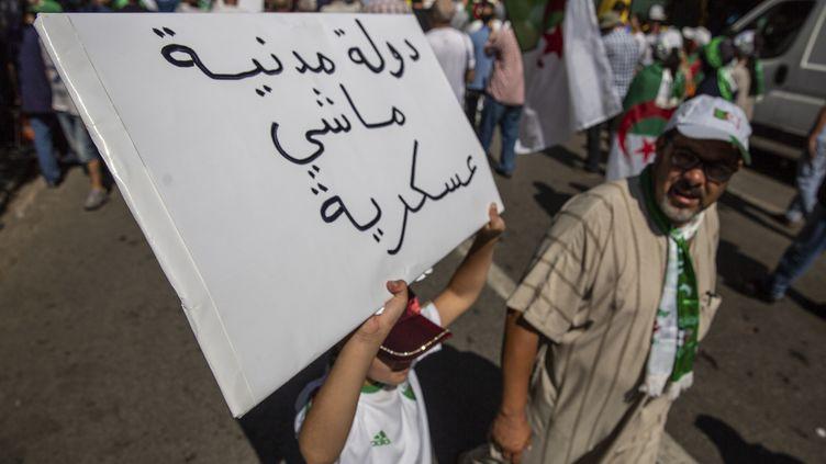 """Un manifestant avec une pancarte """"Etat civil et non militaire"""", le 30 août 2019 à Alger (SOFIANE BAKOURI / HANS LUCAS)"""