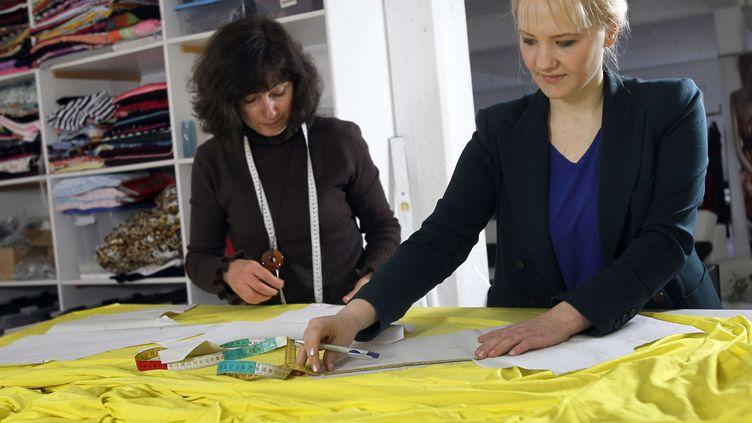 """Anke Domaske (à droite) travaille sur un modèle de robe en """"Qmilch"""", le 8 novembre 2011 à Hanovre (Allemagne). (MICHAEL SOHN / AP / SIPA)"""