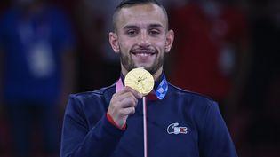 Le Français Steven Da Costa pose avec sa médaille d'or, la première et la dernière de l'histoire du karaté, ce sport n'étant pas retenu au programme olympique de Paris 2024. (ALEXANDER NEMENOV / AFP)