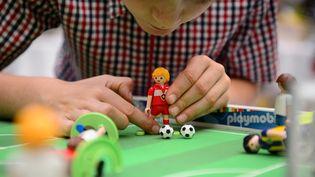 Un enfant joue avec des jouets Playmobil à Londres, le 12 juillet 2014. (LEON NEAL / AFP)