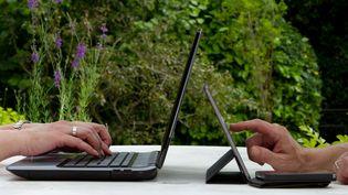 Deux personnes tapent sur un ordinateur et sur une tablette. (TRISTAN MARTIN#93398 / MOMENT MOBILE ED)