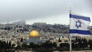 Un drapeau israélien flotte devant la ville de Jérusalem et le dôme du Rocher, le 6 décembre 2017. (MAHMOUD IBRAHIM / AFP)