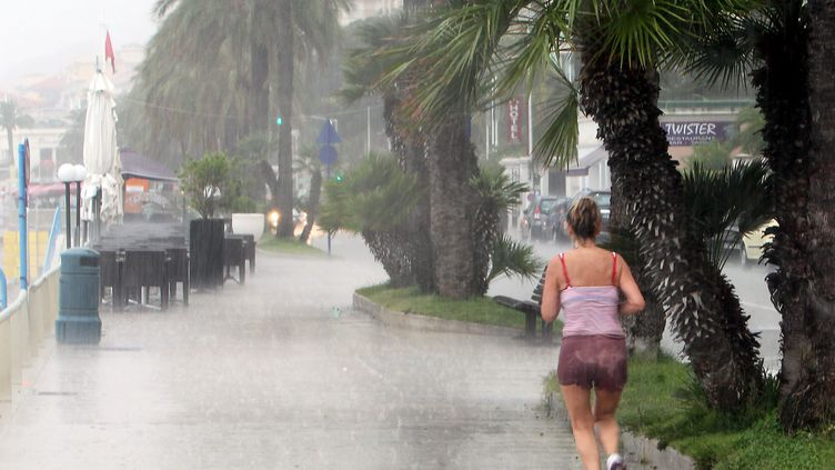 Une femme fait son jogging sous la pluie à Menton (Alpes-Maritimes), le 13 août 2014. (ERIC DULIERE / MAXPPP)