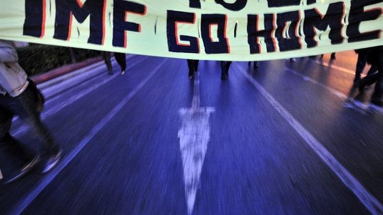"""""""IMF go home"""" (Le FMI dehors). Banderole à Athènes lors d'une manifestation, le 27 avril 2010. (AFP/Aris Messinis)"""