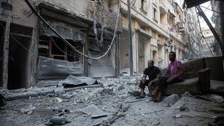 Des habitants d'Alep (Syrie) dans une rue dévastée par un bombardement survenu le 18 septembre 2016, la veille dela fin de la trêve. (KARAM AL-MASRI / AFP)