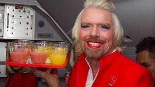 Le milliardaire britannique, Richard Branson joue à l'hôtesse de l'air à bord d'un avion Air Asia à la suite d'un pari perdu à Perth (Australie), le 12 mai 2013. (TONY ASHBY / AFP)