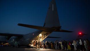Des passagers, notamment afghans, embarquent dans un avion de l'armée française à l'aéroport de Kaboul (Afghanistan), le 26 août 2021, sur une image diffusée par l'état-major des armées. (ETAT MAJOR DES ARMEES / AFP)