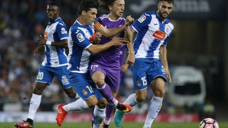 Luka Modric s'infiltre entre deux joueurs de l'Espanol Barcelone (PAU BARRENA / AFP)
