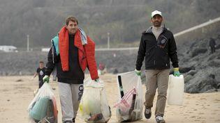 Des passants collectent des déchets, le 20 mars 2015 à Biarritz (Pyrénées-Atlantiques). (IROZ GAIZKA / AFP)