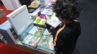 Un enfant lit un livre au salon du livre et de la presse jeunesse à Montreuil (Seine-saint-Denis), le 29 novembre 2017. (JACQUES DEMARTHON / AFP)
