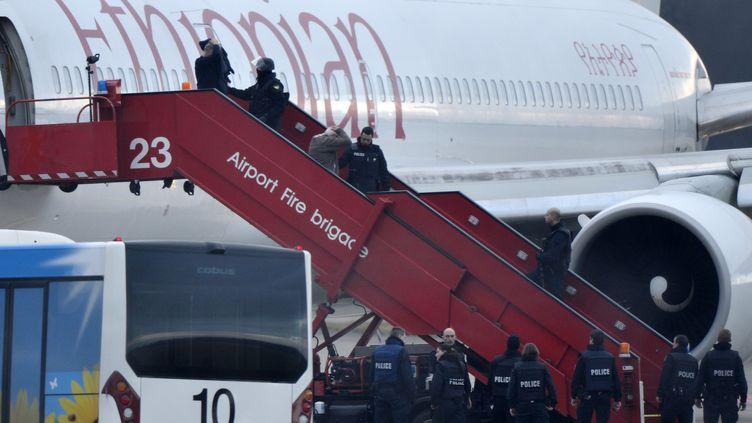 Des policiers suisses évacuent les passagers d'un avion d'Ethiopian Airlines détourné vers Genève(Suisse), le 17 février 2014. (RICHARD JUILLIART / AFP)