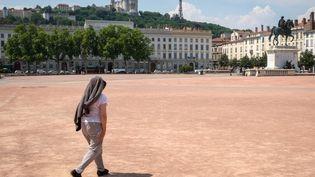 Une femme traverse la place Bellecour à Lyon, le 22 juin 2017, sous des températures atteignant 40°C. (FRANCK CHAPOLARD / CROWDSPARK / AFP)