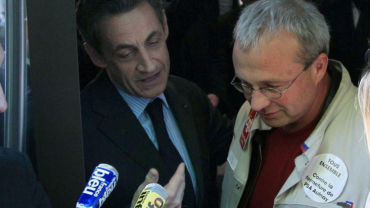 Nicolas Sarkozy raccompagnant à la porte de son QG parisienJean-Pierre Mercier (D), délégué CGT, le 12 avril 2012. (JACQUES DEMARTHON / AFP)