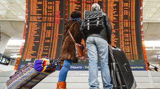 Des passagers vérifient leur porte d'embarquement dans le hall de l'aéroport Roissy-Charles de Gaulle. (ARTUR WIDAK / NURPHOTO)