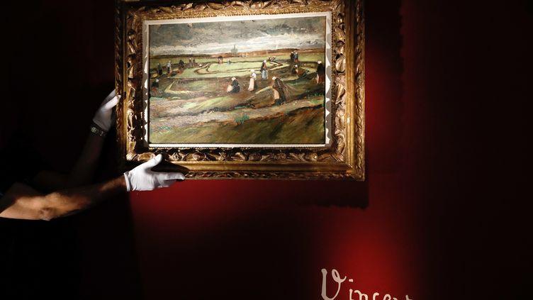 """Le tableau 'Raccommodeuses de filets dans les dunes"""" de Vincent Van Gogh, présenté à la maison de ventes aux enchères Artcurial à Paris est mis aux enchères le 4 juin 2018. (PATRICK KOVARIK / AFP)"""