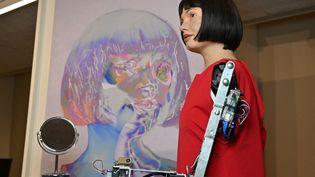 L'artiste-robot Ai-Da et son autoportrait lors d'une exposition au Design Museum de Londres, le 14 mai 2021. (GLYN KIRK / AFP)