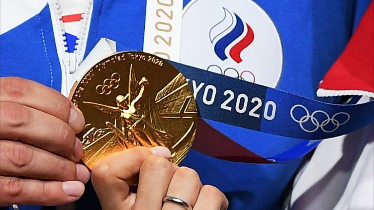 L'escrimeuse Sofia Pozdniakova brandit sa médaille d'or après son sacre olympique dans l'épreuve de sabre, à Chiba, près de Tokyo (Japon), le 26 juillet 2021. (RAMIL SITDIKOV / SPUTNIK / AFP)