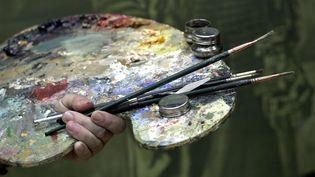 Une palette de peinture et des pinceaux. (DAVID HANCOCK / AFP)