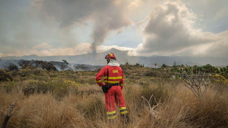 Un pompier face à un nuage de fumées provoqué par l'éruption du volcan Cumbre Vieja sur l'île de la Palma, aux Canaries (Espagne), le 21 septembre 2021. (ANDRES GUTIERREZ / ANADOLU AGENCY)