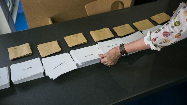 Une électrice prend des bulletins de vote, le 23 avril 2017. (CONSTANT FORME-BECHERAT / HANS LUCAS / AFP)