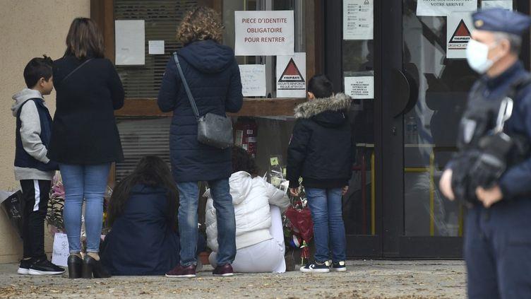 Des gens viennent déposer des fleurs au collège de Conflans-Sainte-Honorine (Yvelines), le 17 octobre 2020, après que l'un de ses enseignants ait été assassiné. (BERTRAND GUAY / AFP)