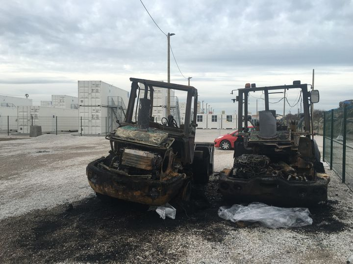 """Deux engins de chantier ont brûlé, dans la nuit du 15 au 16 janvier 2016, sans doute pour protester contre l'installation des conteneurs dans la """"jungle"""". (F. MAGNENOU / FRANCETV INFO)"""